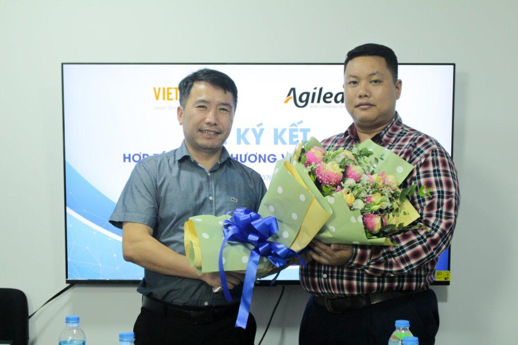 Hai đại diện doanh nghiệp trao tặng hoa sau khi ký kết